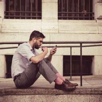 Nuori mies katselee kännykkää.