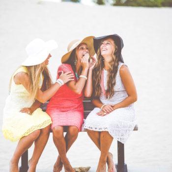 Kolme nuorta naista istuvat rannalla ja nauravat