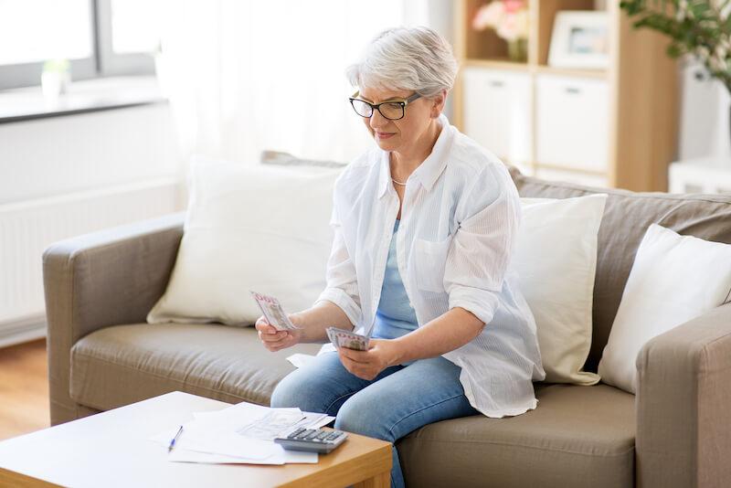 Eläkeläinen nainen laskee seteleitä