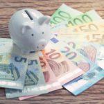 Valkoinen säästöpossu ja erilaisia euron seteleitä.
