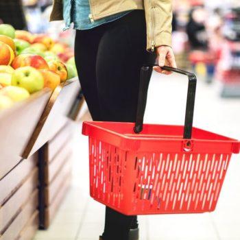 Nainen ostoskorin kanssa ruokaostoksilla kaupassa