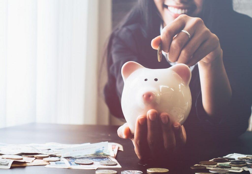 Nuori nainen tallettaa rahaa säästöpossuun.