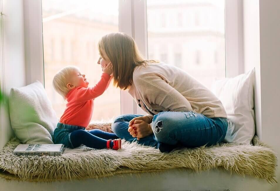 Äiti ja pieni lapsi leikkivät ikkunan luona.
