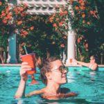 Nuori nainen hotellin uima-altaassa juoma kädessä