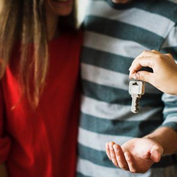Nuori pariskunta vastaanottaa avaimet ASP-lainalla ostamaansa ensiasuntoon