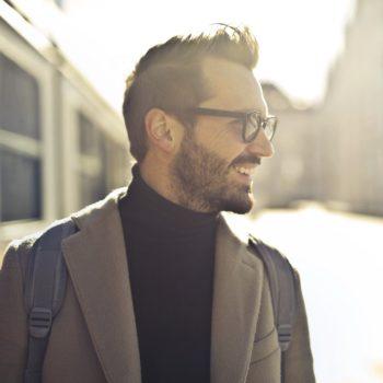Nuori mies ruskeassa takissa hymyilee saatuaan apua lainan hakemiseen