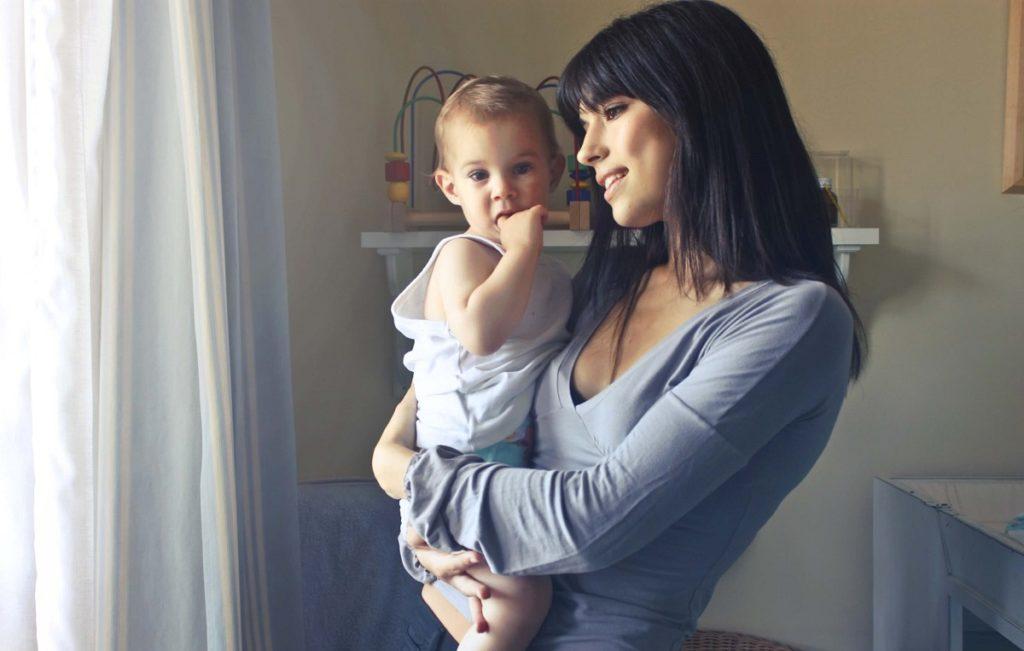 Nuori äiti pitelee vauvaa sylissään heidän uudessa asunnossaan