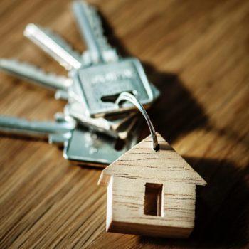 Juuri ostetun asunnon avaimet pöydällä puisen talonmuotoisen avaimenperän kanssa