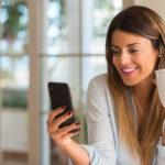 Hymyilevä nainen hakee Bank Norwegian-korttia kännykän kautta