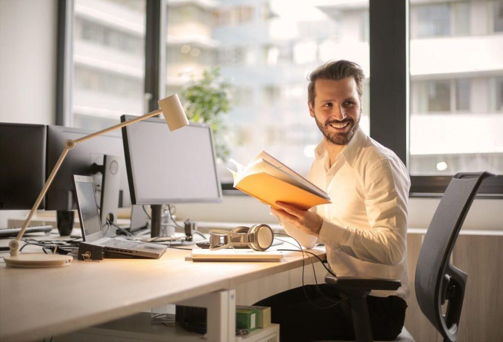 Nuori yrittäjä hymyilee toimistossaan saatuaan bullet lainan yritystään varten