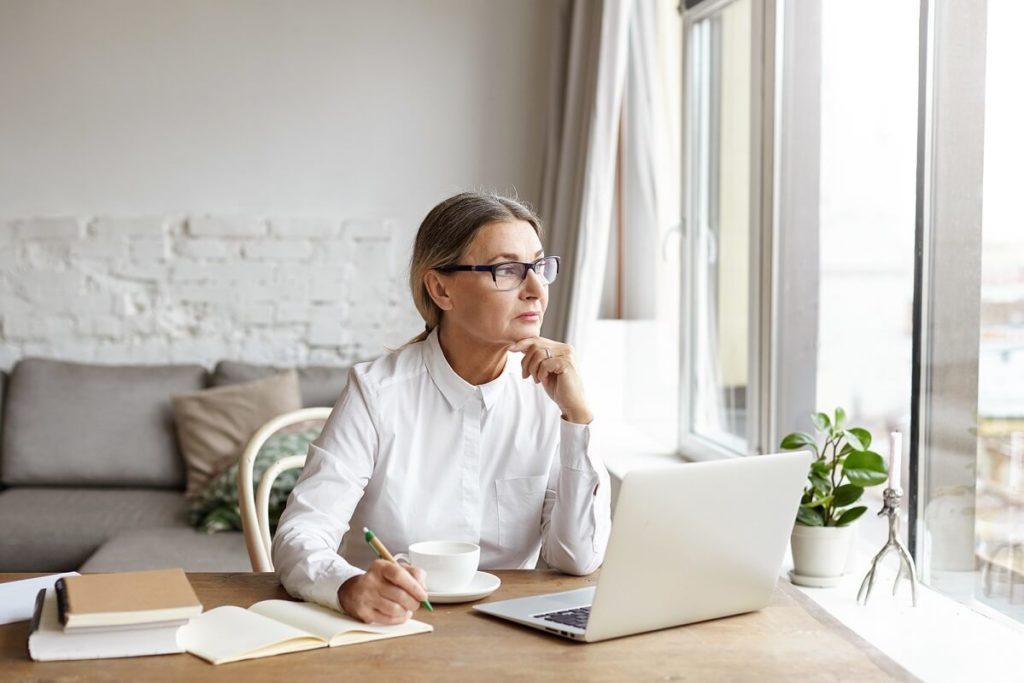 Tyylikäs eläkeläis nainen täyttää lainahakemusta pikavippiä varten