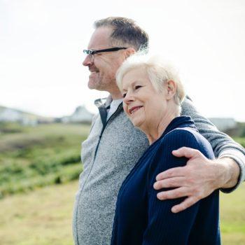 Vanha pariskunta seisoo nurmella yhdessä ja miettii käänteisen asuntolainan ottamista