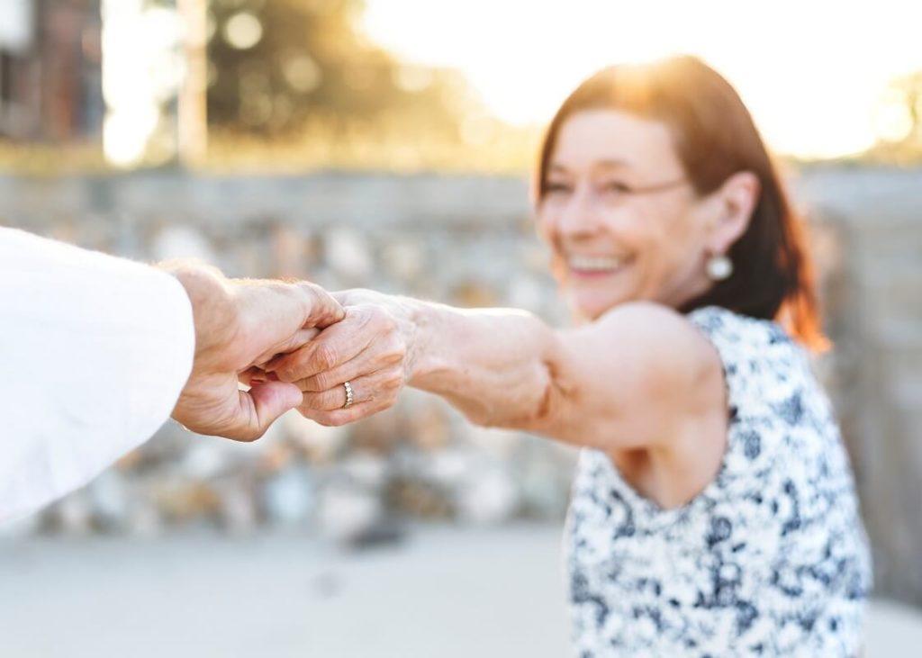 Iäkäs pariskunta pitelee toisiaan kädestä kiinni onnellisina