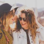 Kaksi hymyilevää naista nauravat yhdessä