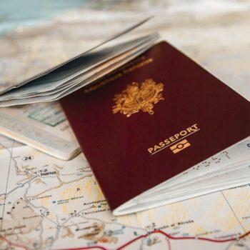 Kuva kahdesta ulkomaalaisesta passista kartan päälle aseteltuna