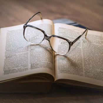 Kuva aukiolevasta sanakirjasta, jonka päällä on silmälasit