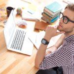 Nuori silmälasipäinen mies pohtii lainaturvavakuutuksen ottamista
