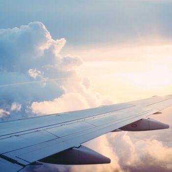 Kuva lentokoneen siivestä pilvisellä taivaalla. Lentopisteitä voi käyttää lentojen ostoon