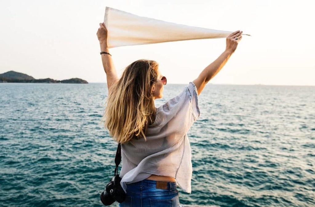 Kaunis nainen seisoo merenrannalla lomamatkalla, jonka lennot hän on ostanut lentopisteitä käyttämällä