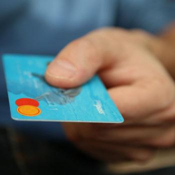 Mies pitelee kädessään sinistä luottokorttia