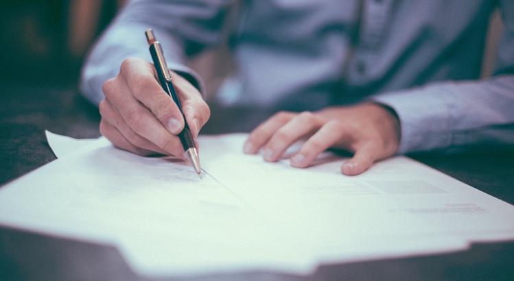 Mies täyttää kirjallista pyyntöä luottotietojen tarkistamiseen
