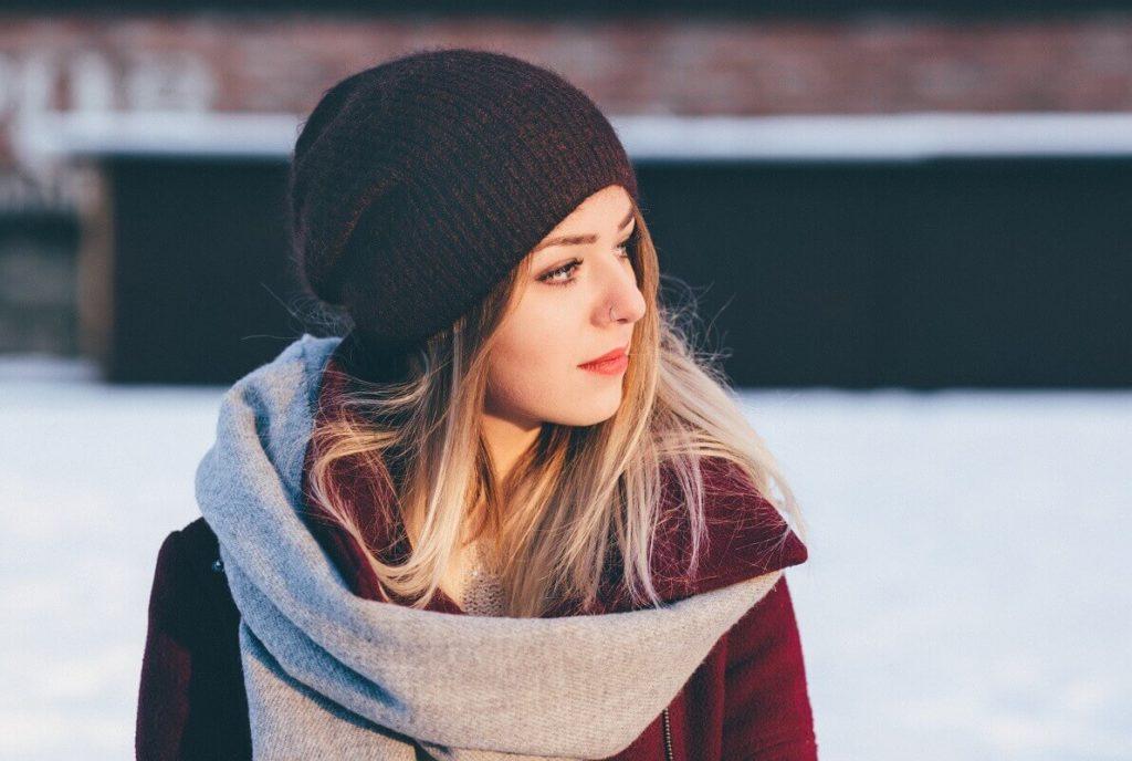 Nuori nainen talvivaatteissa pohtii, millaisia seurauksia maksuhäiriömerkinnällä on hänelle