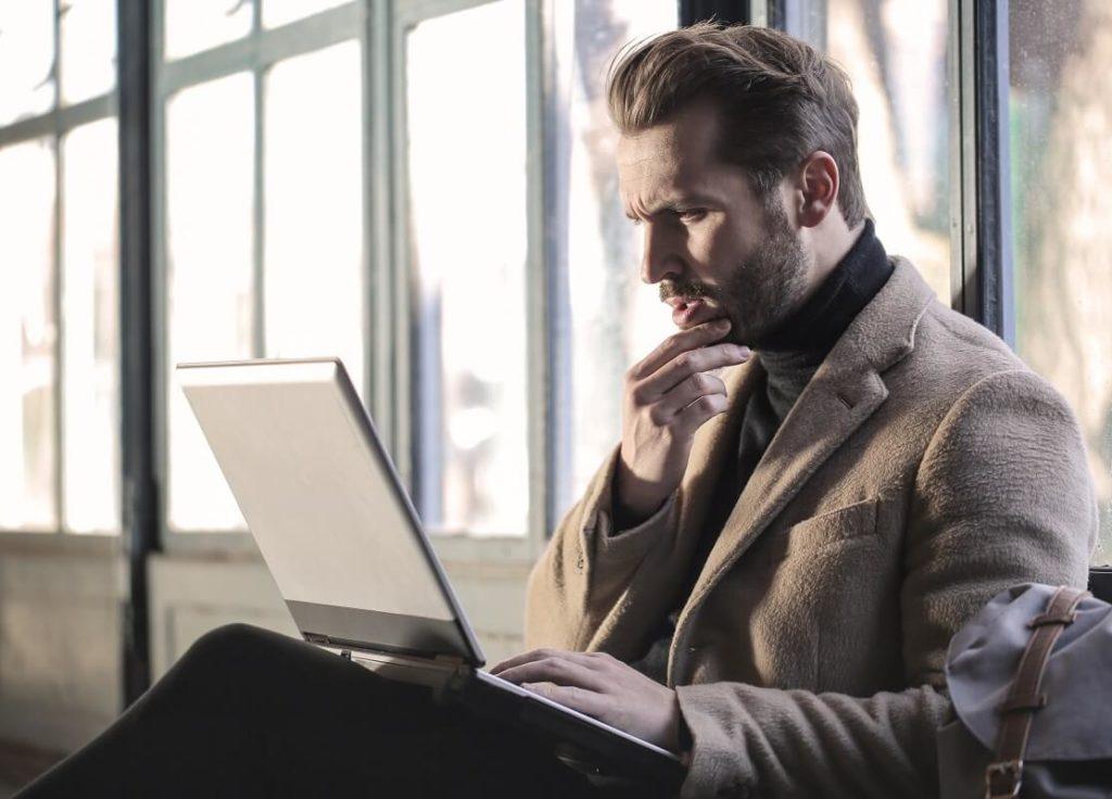 Nuori mies katsoo huolestuneena kannetavan tietokoneensa ruutua saatuaan tietää, että hän on saanut maksuhäiriömerkinnän