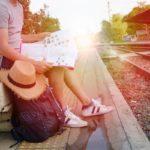 Matkailija istuu juna-asemalla lukemassa karttaa