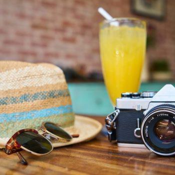 Kuva aurinkolaisesita, kamerasta, hatusta ja hienosta drinkistä. Kulutusluotolla pääset vaikka ulkomaanmatkalle