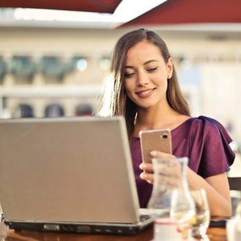 Kaunis nuori nainen hymyilee kännykälle saatuaan hakemansa lainan heti tilille