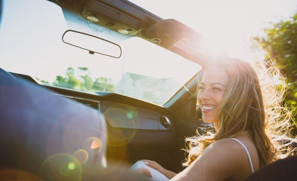 Kaunis nuori tyttö hymyilee uuden auton kyydissä auringonpaisteessa