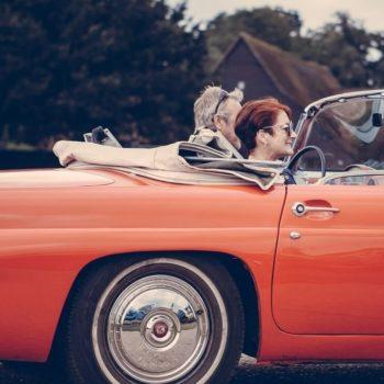 Vanhempi pariskunta ajaa punaisella autolla, jonka he ovat juuri ostaneet autolainalla