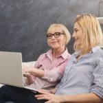 Äiti ja aikuinen lapsi kirjoittavat velkakirjaa korottomasta lainasta kannettavalla tietokoneella