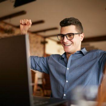 Nuori mies juhlii tietokoneen ääressä maksettuaan laskunsa ja päästyään eroon velkakierteestä