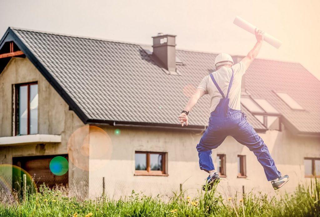 Remonttimies hyppii innoissaan ylös remontoitavan talon edustalla talopiirrustukset käsissään
