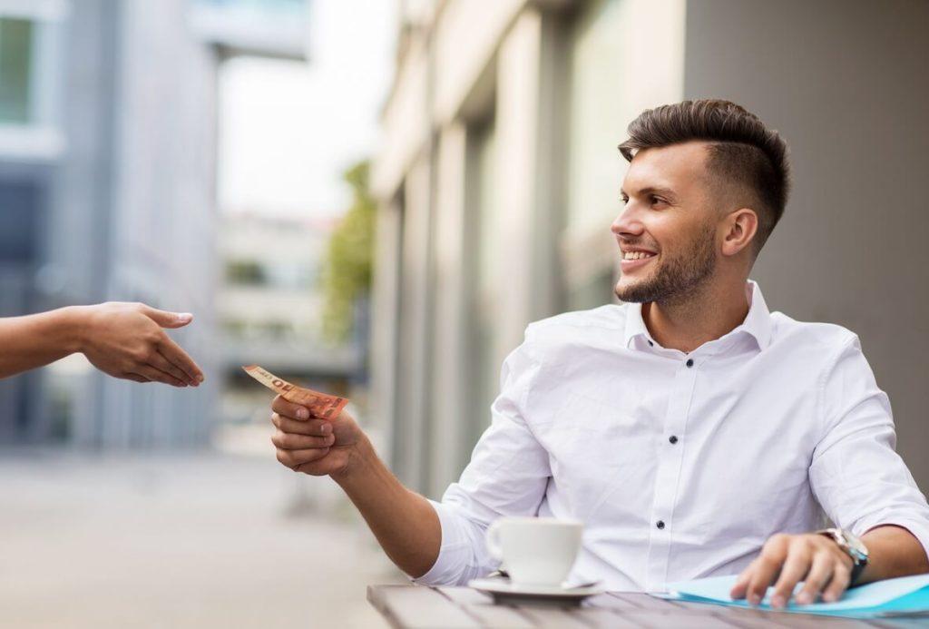 Komea nuori mies maksaa käteisellä kahvilassa ulkomailla