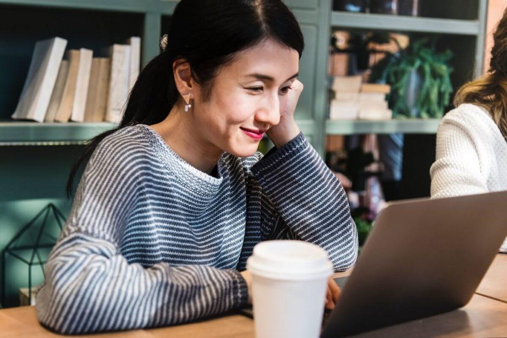 Kaunis nainen täyttää kannettavalla tietokoneella lainahakemusta