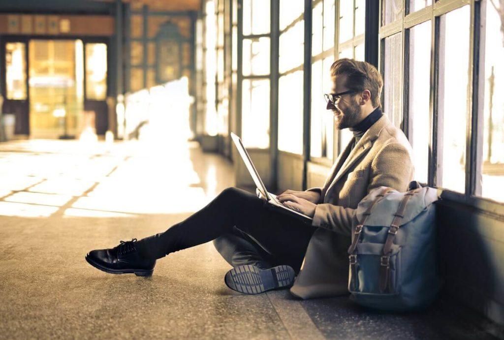 Ulkomailla matkustava mies vastaanottaa Western Union rahalähetyksen pankkitililleen
