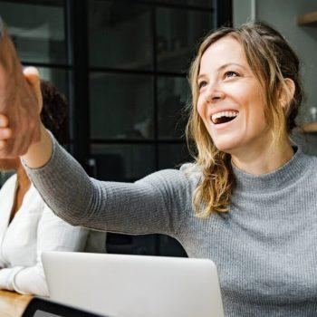 Iloinen nainen kättelee pankkivirkailijaa lainaneuvottelun päätteeksi