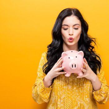 Tyttö pitelee käsissään vaaleanpunaista säästöpossua