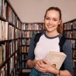 Opiskelija seisoo koulun kirjastossa oppikirja kädessään