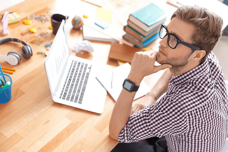 Nuori opiskelija lukee tietokoneelta päätöstä hänen saamastaan opintolainahyvityksestä