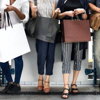 Joukko ystävyksiä kantavat ostospusseja ollessaan yhdessä shoppailemassa