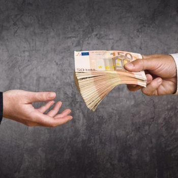 Mies ojentaa setelinipun toiselle miehelle. Karsimalla pois tarpeettomat vakuutukset voit säästää rahaa.