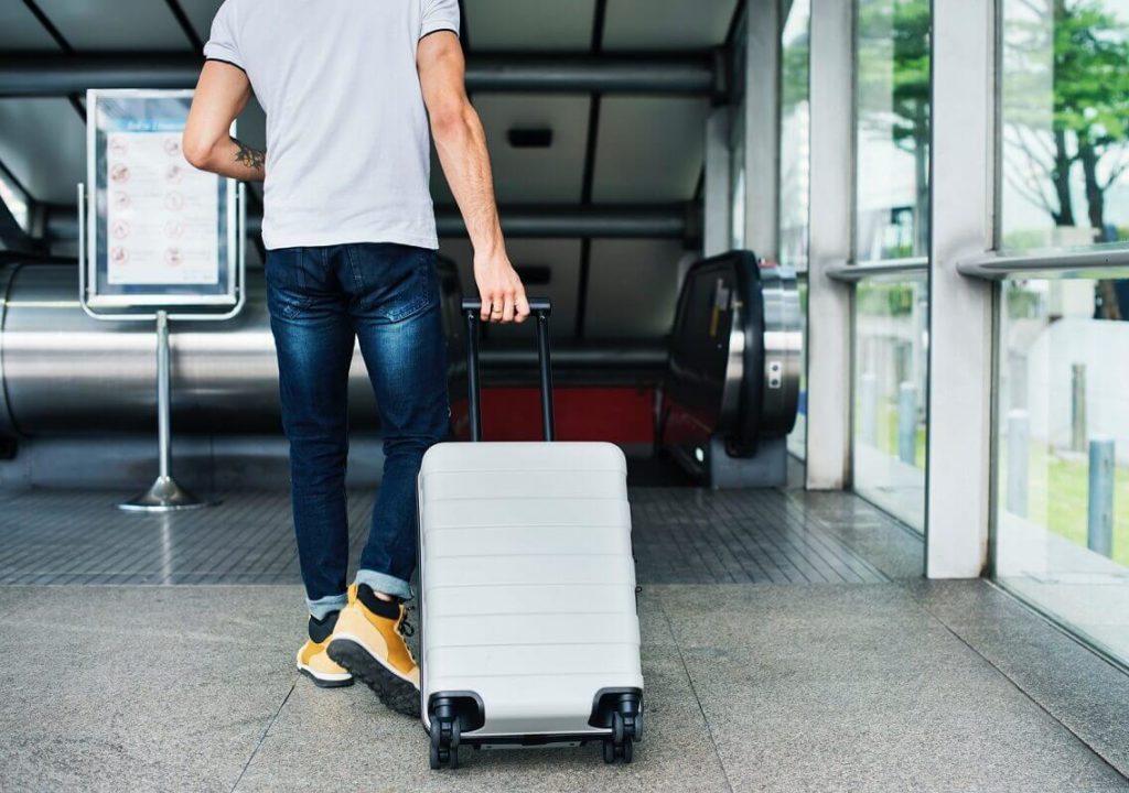 Mies kävelee lentokentällä matkalaukun kanssa. Lentopisteitä voi käyttää muun muassa lounge-pääsyihin