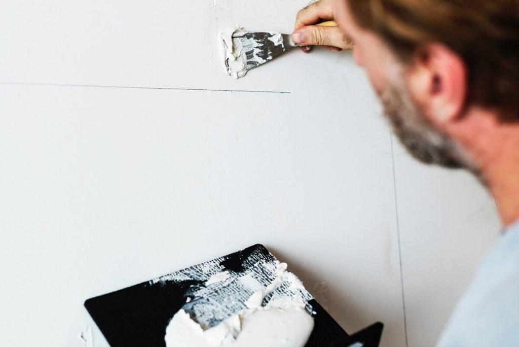 Mies maalaa seinää valkoisella maalilla haettuaan remonttia varten remonttilainaa