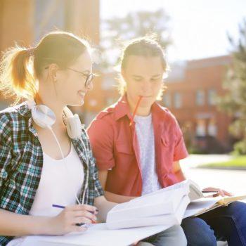 Kaksi opiskelijaa istuvat koulun ulkopuolella oppikirjojen kanssa