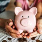 Työtön pariskunta pitää vaaleanpunaista säästöpossua kädessään ja laskevat rahojaan