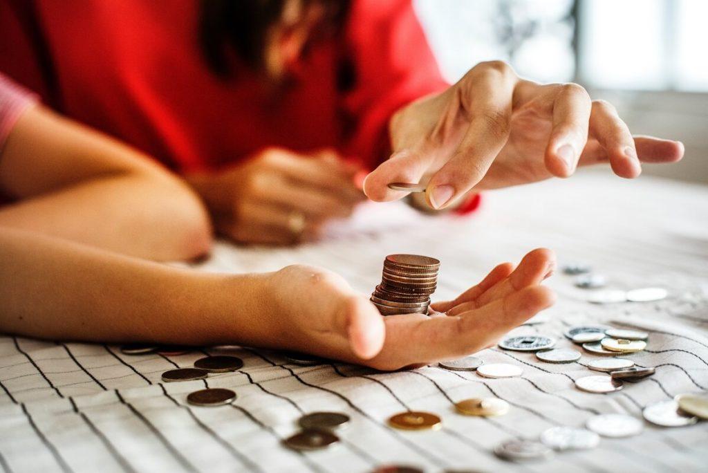 Työtön pariskunta laskee kolikoita pöydällä ja pohtii pikavipin ottamista