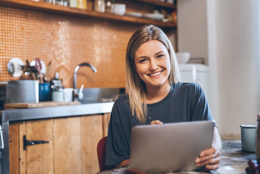 Kaunis, nuori nainen täyttää Raha.fi:n lainahakemusta tietokoneellaan